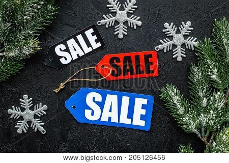 Winter sale. Sale labels near spruce branches on black background top view.