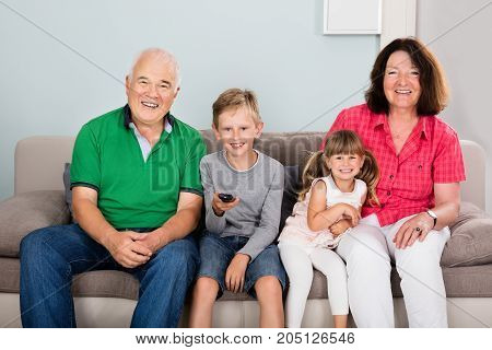 Happy Grandparents With Grandchildren Sitting On Couch In Living Room Watching Television