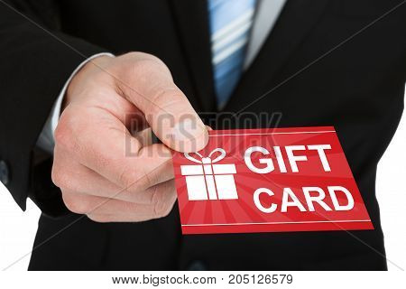 Close-up Of Businessman Hand In Suit Giving Red Gift Card