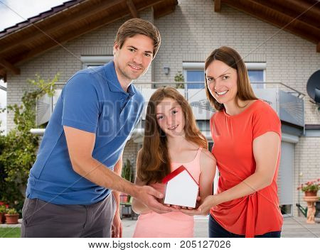 Daughter With Their Parents Standing In Front Of Their House Holding House Model