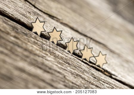 Five stars in a row on a rustic wooden boards. Conceptual of service rating and quality of trade.