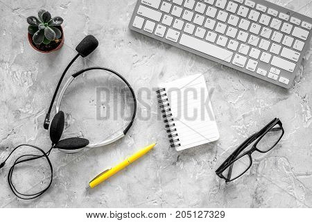 Worktable in call center. Headphones, keyboard and notebook on grey background top view.