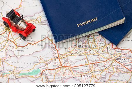 Toy car with two passports on the background of the map, background