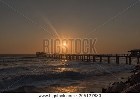 Silhouette of the historic jetty and anglers against the setting sun in Swakopmund in the Namib Desert on the Atlantic Coast of Namibia