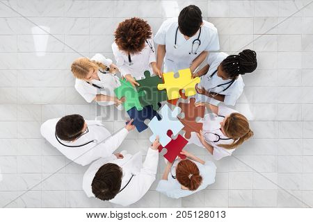 Elevated View Of Doctors Standing In Circle Holding Colorful Puzzle In Hospital