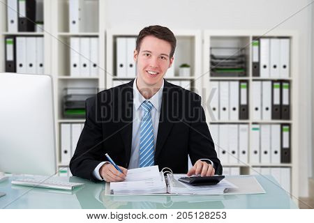 Portrait Of A Happy Young Accountant Calculating Invoice