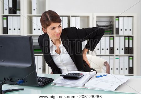 Unhappy Businesswoman Suffering From Back Pain In Office