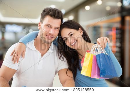 Portrait Of Young Smiling Couple With Small Multi Colored Shopping Bags