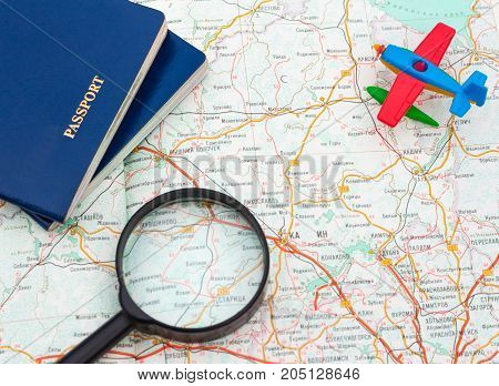 Miniature airplane, passport and magnifying glass on map , travel around the world, wallpaper