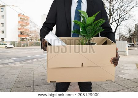 Mid Section View Of A Businessperson's Hand Carrying Belongings In Cardboard Box