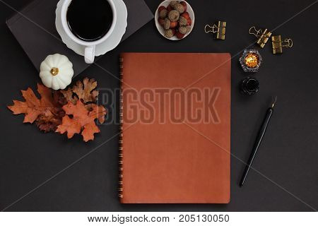 Autumn styled desk top from above with nature items, coffee, office supplies and blank planner.