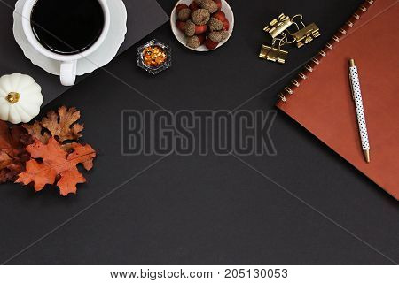 Autumn styled desk top in black and brown colors. Nature accents, office supplies and copy space.