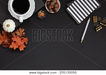 Autumn styled dark desktop in black, white and orange. Office supplies, nature items and coffee. Copy space.