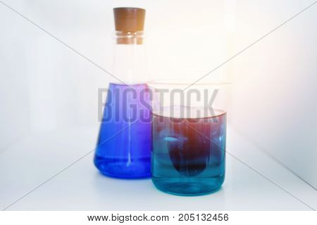 Test tubes for chemical experiments with blue liquid, green, glare of light.