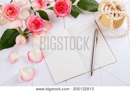 Open blank diary or journal for text with a ballpoint pen pink roses and pearls on wooden desk overhead view romantic concept