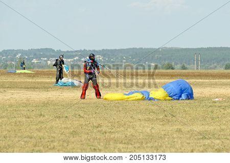 Kharkiv Ukraine - August 26 2017: Skydiver unfasten his parachute after landing at the airfield Korotych Kharkov region Ukraine on August 26 2017