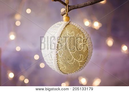Handmade Linen and lace Christmas tree ball with ornament hanging on a branch. Golden garland glittering light in the background. Festive greeting card poster template. Copy space.
