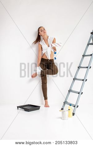beautiful attractive woman painting wall with paint roller in house