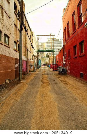 Looking down a long city alley with graffiti.