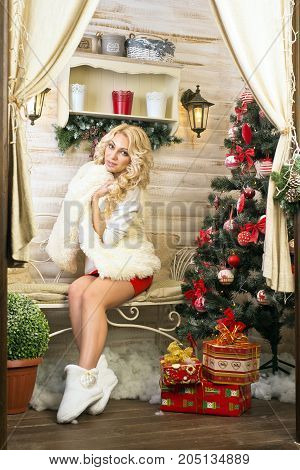 Christmas Celebration. A blonde girl  wrapped in a warm blanket sitting on a bench near a Christmas tree decorated with toys,. Volgograd. Volgograd region. November 8, 2015