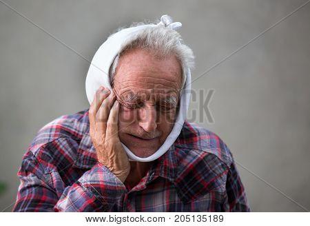 Senior man having toothache and holding bandage around head