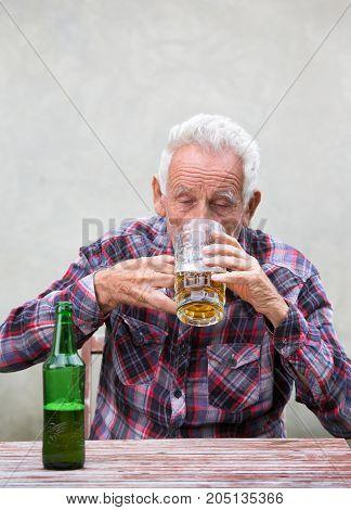 Senior Man Drinking Beer From Mug