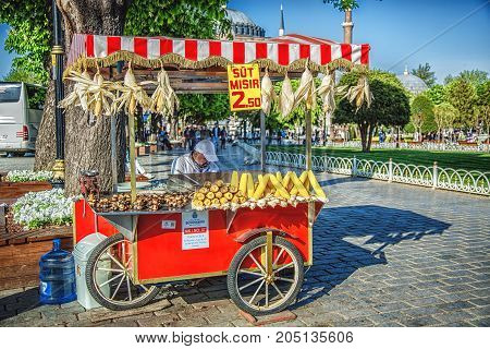 ISTANBUL TURKEY - MAY 2 2017: Seller of street fast food with boiled and grilled corn and chestnut on traditional turkish cart. At Sultanahmet square