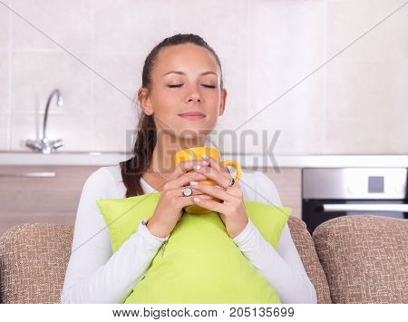 Girl With Pillow And Cup Of Coffee On Sofa