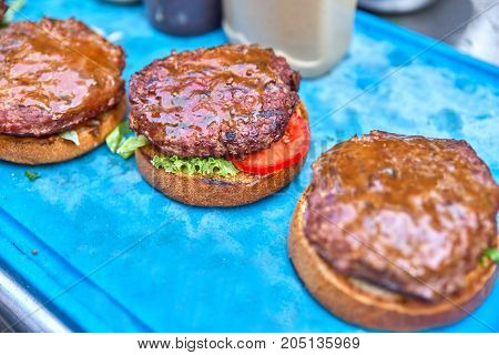 hamburgers are prepared by adding sauce to cream cheese. Three hamburgers. At work. On a blue board, close-up.