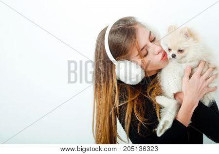 New year of dog and winter holiday celebration. Girl with happy face in gloves and ears. Xmas party and vacation. Dog in hand of woman on white background. Woman with small dog of Pomeranian Spitz.