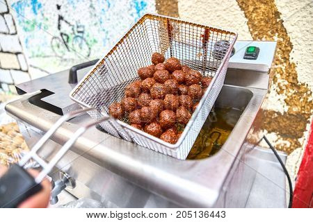 Falafel is being prepared - a dish of deep-fried balls from chopped chickpeas, with the addition of beans, seasoned with spices.