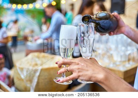 woman's hand with two glasses of champagne. Pours in them champagne. Picnic. Romantic date. Celebration. on the background of people in the background.