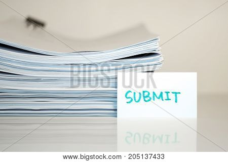 Submit; Stack Of Documents On White Desk And Background.