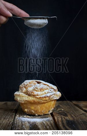 Hand sprinkling powdered sugar on a Mirliton cupcake traditional sweet of France and Basque Country Spain.