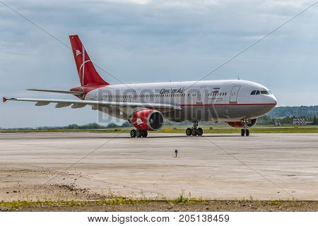 Pulkovo, Saint-Petersburg, Russia - August 10, 2017:   The airplane Airbus A300 of Qeshm Air is landing on the runway against the background of the forest and blue sky. Summer sunny weather