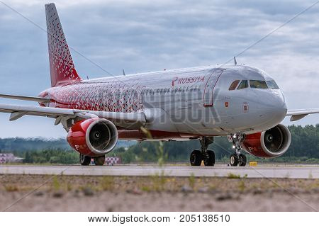Pulkovo, Saint-Petersburg, Russia - August 10, 2017:   The airplane Airbus A320 of Rossiya Airlines is taxi on the runway against the background of the forest and blue sky. Summer sunny weather