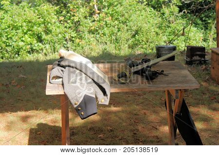 Confederate officer's short jacket and sword sitting on wooden table at a Civil War reenactment.