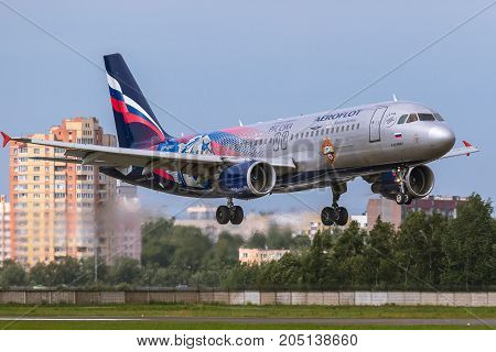 Pulkovo, Saint-Petersburg, Russia - August 10, 2017:   The airplane  Airbus A320 of Aeroflot  airlines is landing on the runway against the background of the city skyline. Has a special livery - PFC CSKA