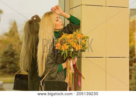 Portrait of a young girl in a lovely autumn day with a bouquet of yellow and orange with satin colored ribbons