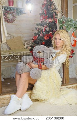 Girl sitting on a veranda threshold which is decorated Christmas fir tree. gently hugs a teddy bear. The legs which are covered by a white blanket Volgograd region Russia November 8 2015