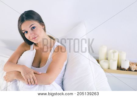 A pretty young woman sitting in bed
