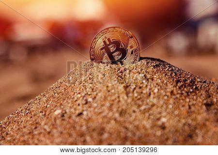 Bitcoin on golden sand, in background sun light