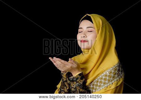 religious young Muslim woman praying over black background.