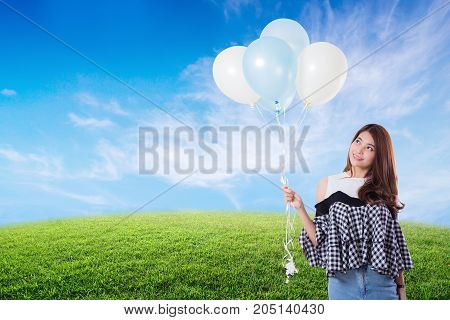 Young woman holding balloons on meadow summer with freedom lifestyle concept.