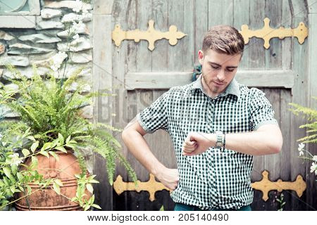 Man standing at garden looking at hand watch - Time is money.