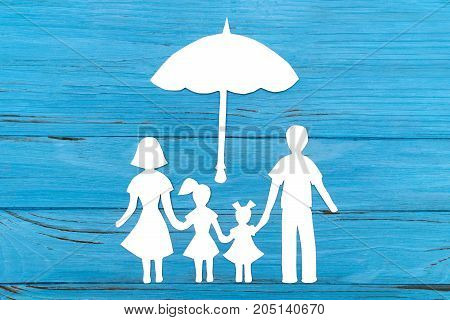 Paper silhouette of family under umbrella on blue wooden background. Life insurance concept