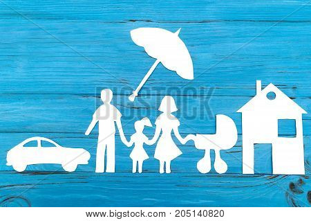 Paper silhouette of family with baby carriage under umbrella, car and house on blue wooden background. Life insurance concept