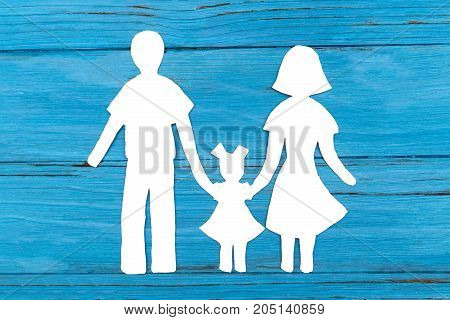 Paper silhouette of family on blue wooden background. Concept of family love