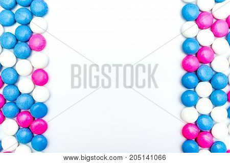 Top view of frame made of colored chocolate coated candy. Isolated on white background. Copy space