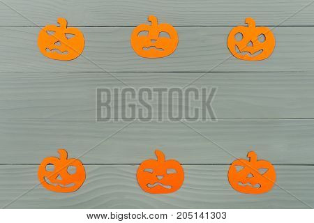 Top view of paper silhouette of six different pumpkin made of horizontal frame on grey wooden background. Halloween holiday background. Copy space